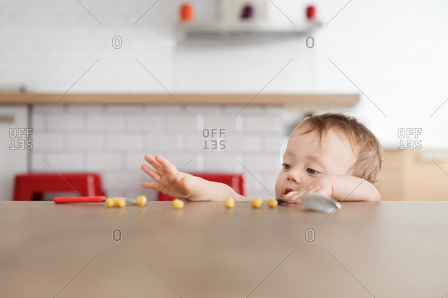 Baby reaching for pieces of cereal on table