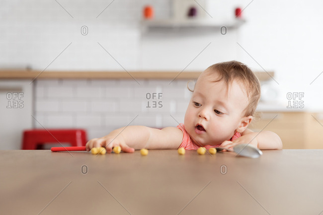 Baby grabbing for pieces of cereal on table