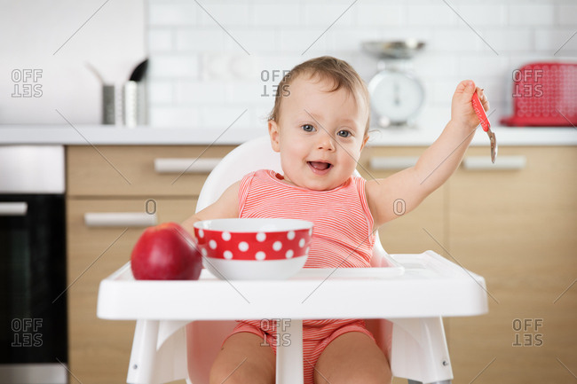 Happy baby eating in a high chair
