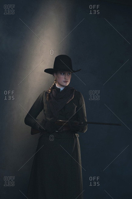 Dangerous vintage Victorian Western woman shooting with rifle