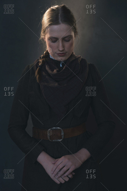 Dark portrait of vintage Victorian Western woman with hands crossed