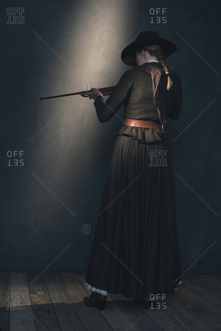 Dangerous vintage Victorian Western woman in brown dress and hat shooting with rifle