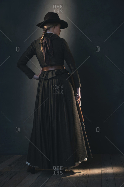 Eerie vintage Victorian Western woman in brown dress and hat standing with rifle