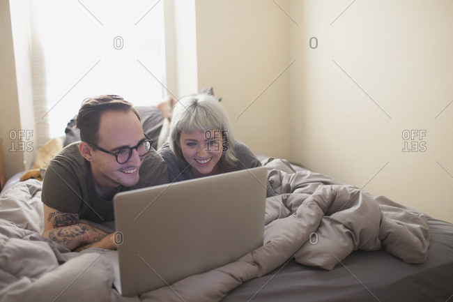 Young couple lying in bed looking at a laptop