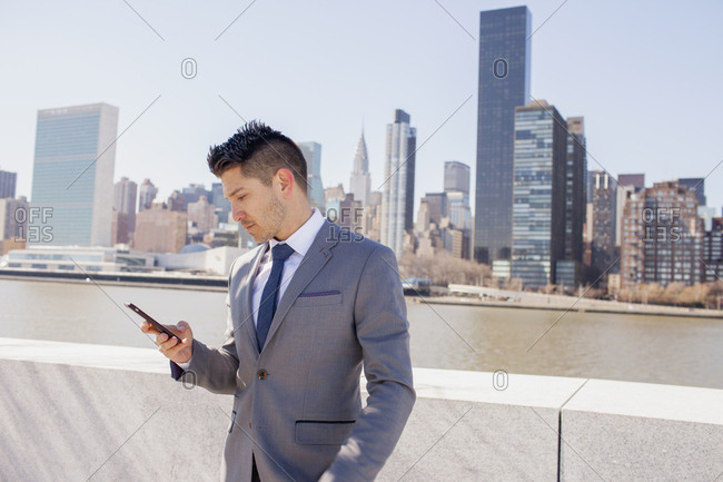 Portrait of young business man in urban environment looking at smartphone