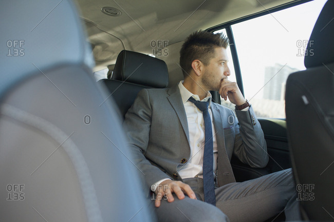 Young business man looking out the window sitting in car service limousine