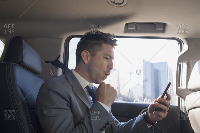 Young business man looking at smartphone sitting in car service limousine