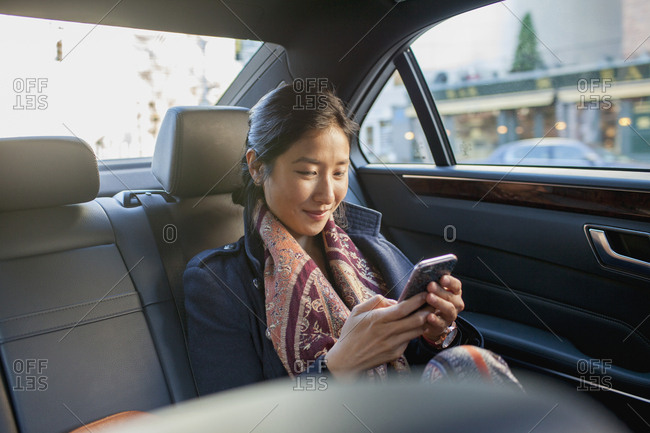 Young Asian business woman looking at smartphone sitting in car service limousine