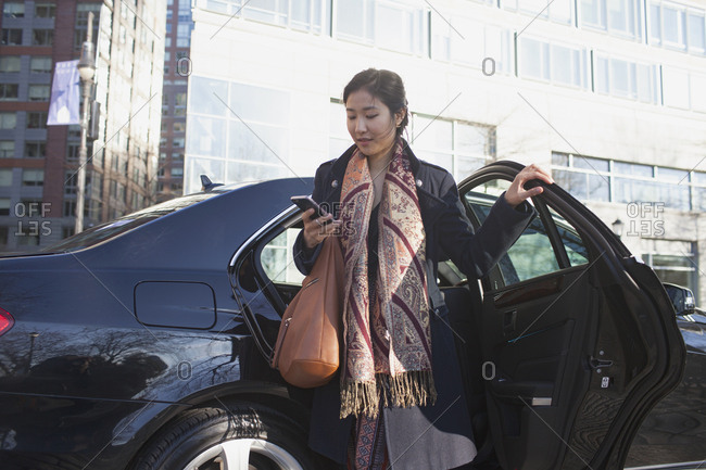 Young Asian business woman getting out of car service limousine