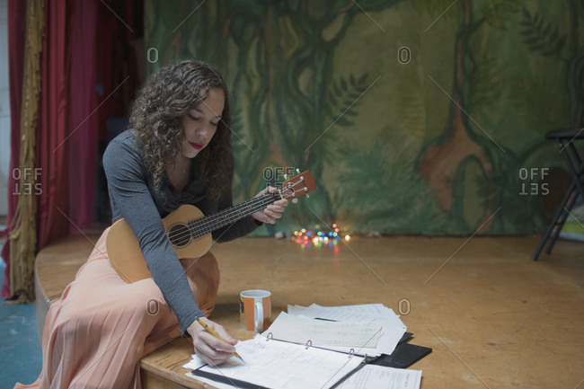Young female musician composing music with the Ukulele