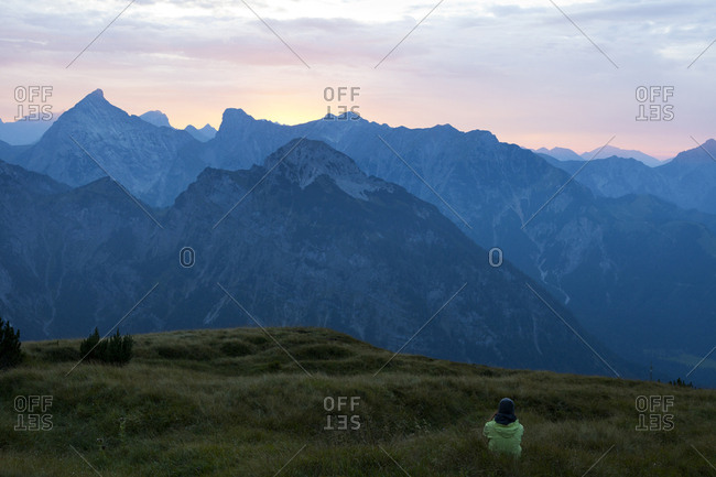 Austria- Tyrol- hiker sitting in alpine meadow at twilight