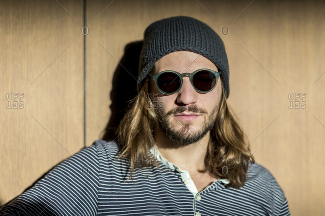 Portrait of bearded man with long hair wearing sunglasses and wooly hat  stock photo - OFFSET 3cbdb01118f8