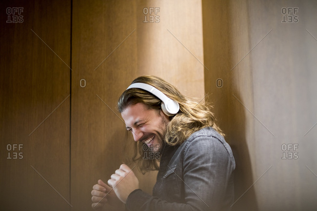 Portrait of excited man listening music with headphones