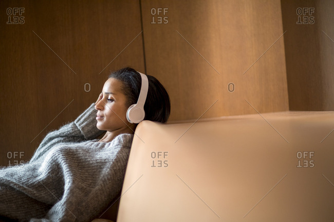 Portrait of relaxed young woman listening music with headphones on couch