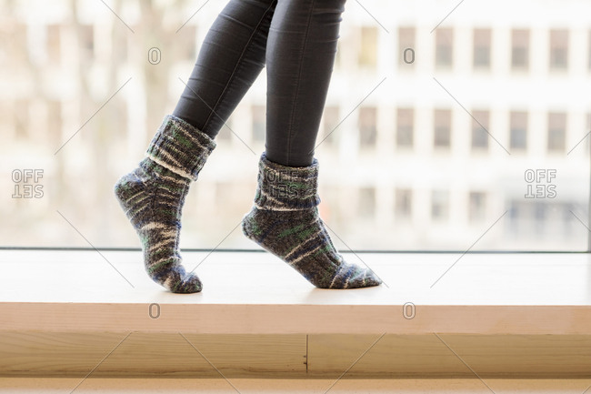 Woman wearing knitted socks balancing on window sill- partial view