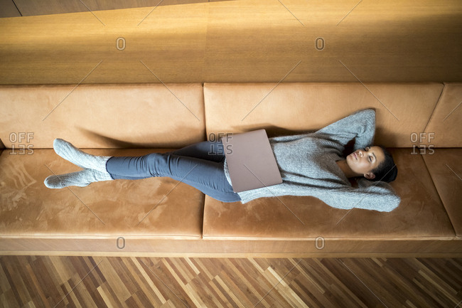 Woman with laptop relaxing on couch