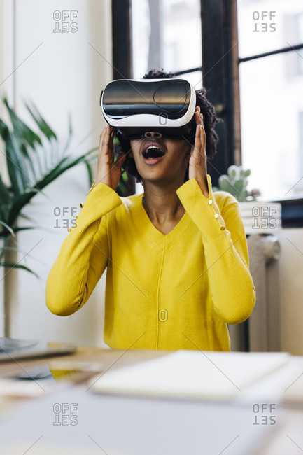 Laughing young woman playing game- wearing virtual reality goggles