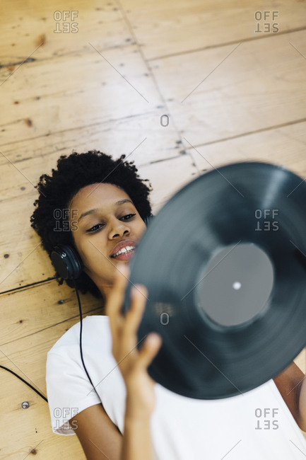 Young woman at home listening vinyl records- lying on ground