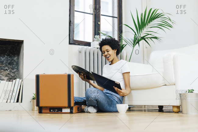 Young woman sitting on ground listening music from record player