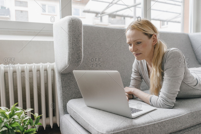 Woman lying on couch using laptop