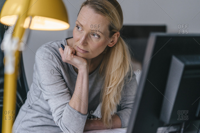 Woman sitting at desk thinking