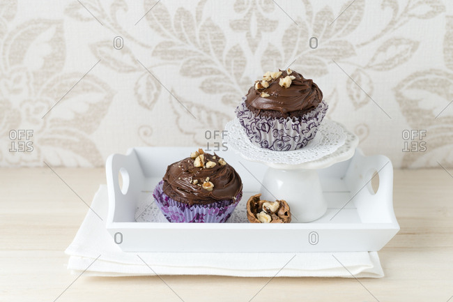 Two cup cakes with chocolate cream and cracked walnuts in paper cup