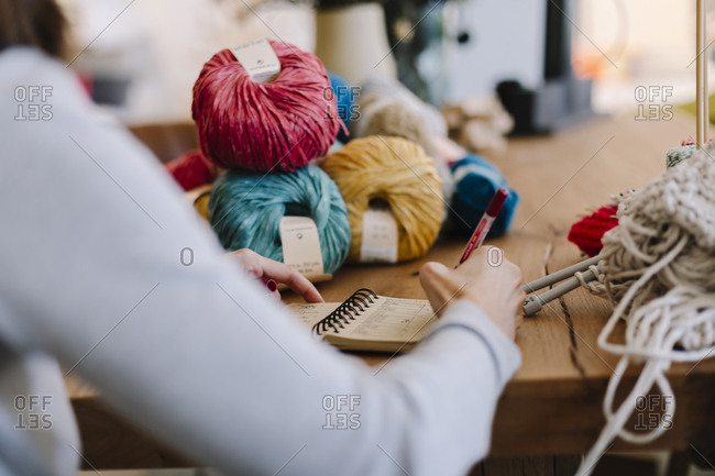 Close-up of woman taking notes on table with knitting