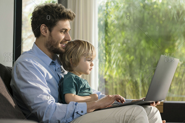 Father and son looking at laptop on couch at home
