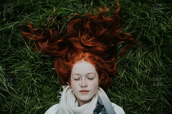 Young redhead woman lying peacefully in grass with long hair spread out