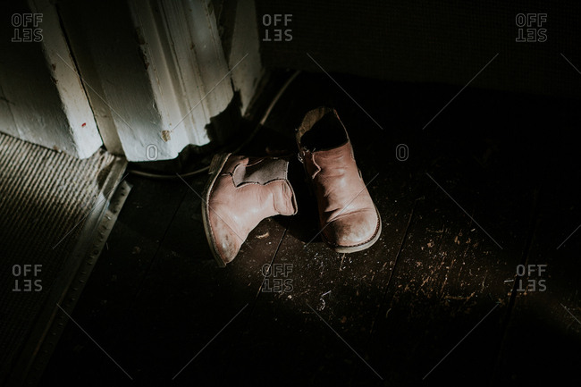 Discarded leather children's boots on floor in dark room