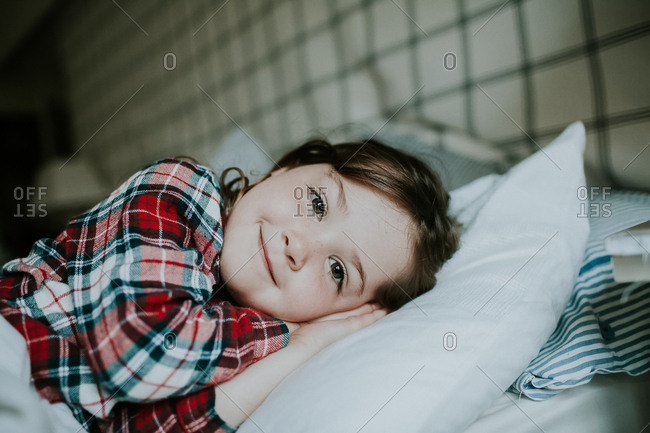 Happy little girl resting on comfortable bed