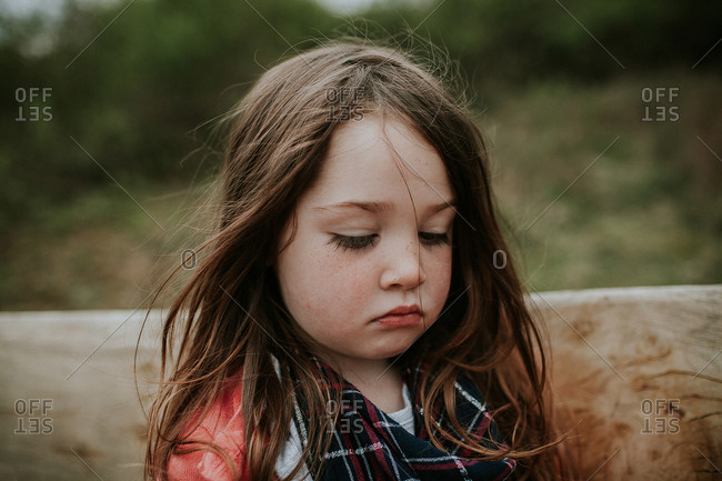 Young girl standing quietly outside alone