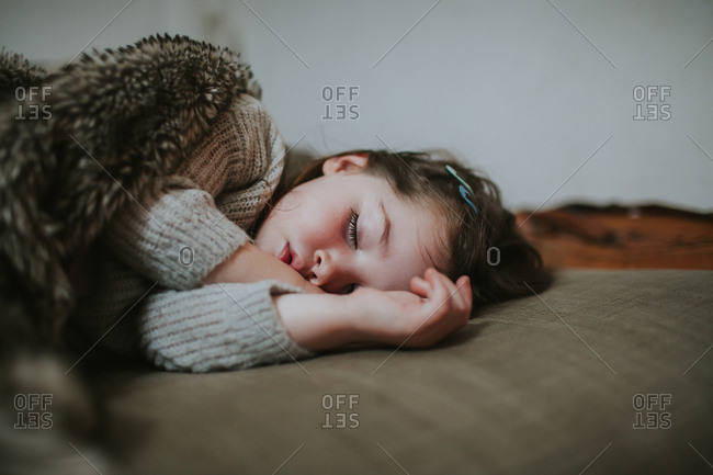 Small child sleeping peacefully with fuzzy blanket