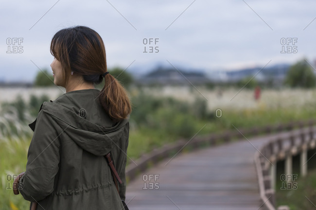 Woman standing on boardwalk in natural area