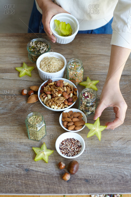 Person arranging starfruit pieces among bowls of whole grains and nuts