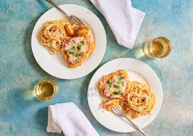 Chicken parmesan and spaghetti dinner with white wine