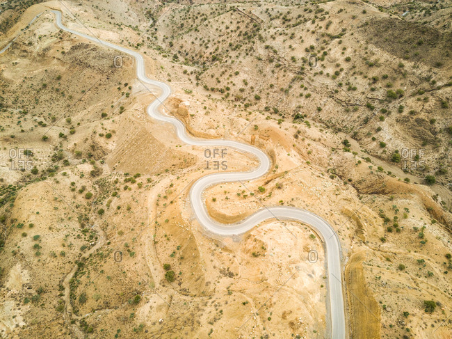 Aerial view of a serpentine empty road in the deserted landscapes of Ethiopia.
