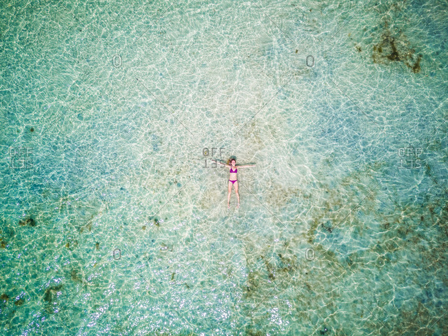 TANZANIA - February 19 2017 : Aerial view of a woman floating in idyllic sea on Mafia island, Tanzania.