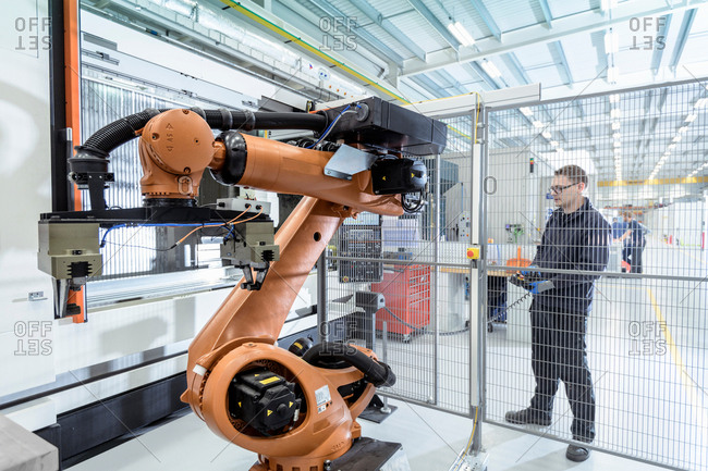 Robotics engineer operating robot aided CNC machine in robotics research facility