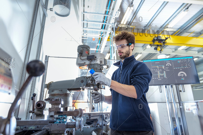 Robotics engineer fitting sensors to traditional engineering lathe in robotics research facility
