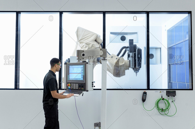 Robotics engineer operating robot cutting machine in robotics research facility