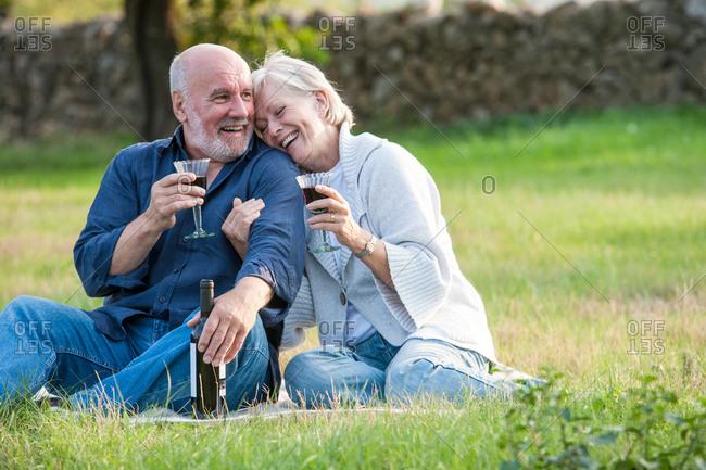 Senior couple outdoors, sitting on blanket, enjoying glass of wine