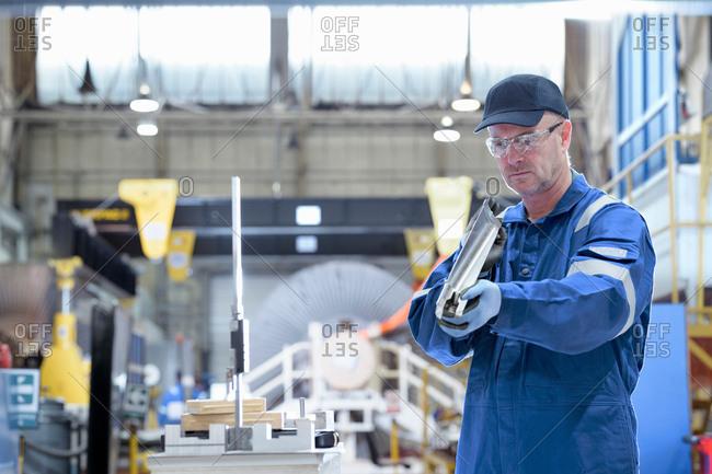 Engineer inspecting turbine blade in turbine maintenance factory