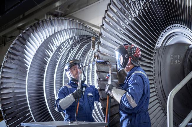 Engineers brazing ends of blades on low pressure steam turbine in turbine maintenance factory