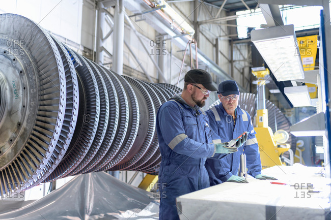 Engineers inspecting turbine blade in turbine maintenance factory