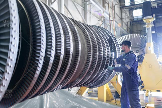 Engineer working on high pressure steam turbine in turbine maintenance factory
