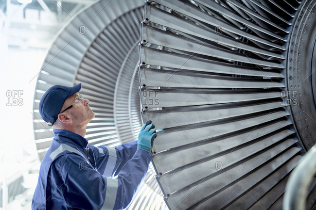 Close up of engineer inspecting low pressure turbine during inspection in turbine maintenance factory