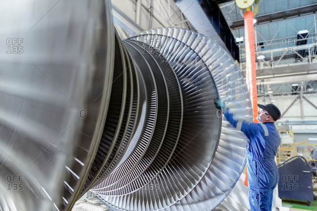 Engineer turning low pressure steam turbine during inspection in turbine maintenance factory