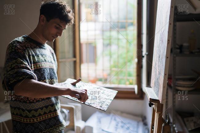 Male artist applying oil paint to palette in artists studio