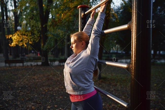 Curvaceous young woman training, gripping exercise bar in park